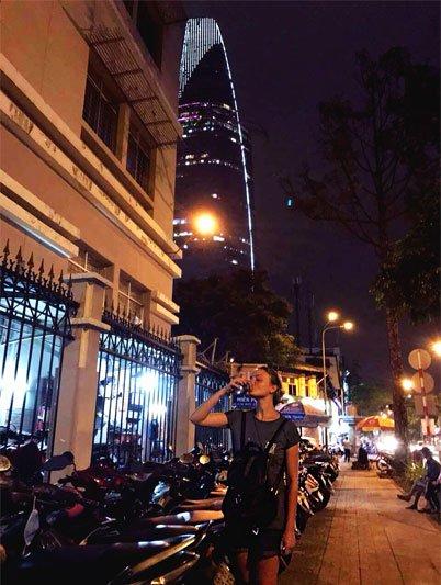 Mergina geriantį vandenį Vietnamo gatvėje