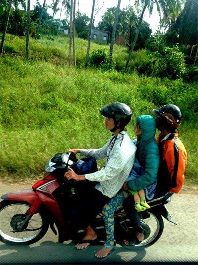 Trys berniukai važiuojantys ant vieno motorolerio Vietname