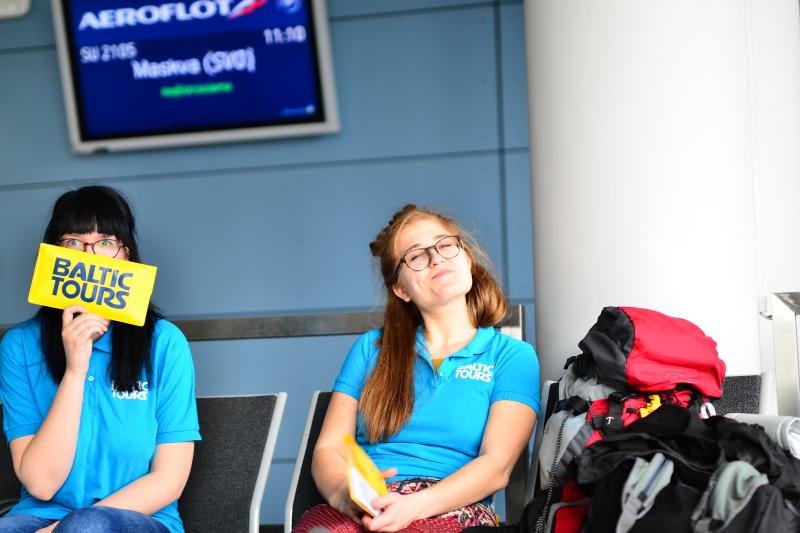 Besišypsanti mergina Vilniaus oro uoste, turizmo agentūra
